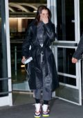 Bella Hadid wears a leather coat over a grey sweatsuit as she lands at JFK airport in New York City