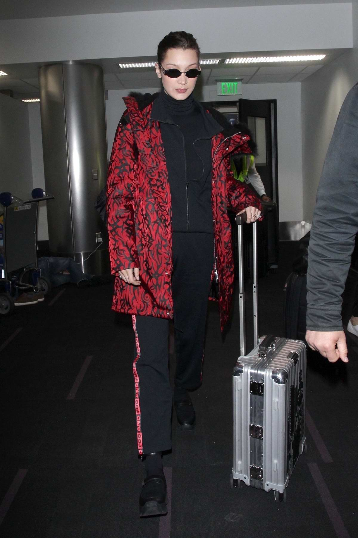 Bella Hadid wears a red and black patterned jacket as she lands at LAX airport, Los Angeles