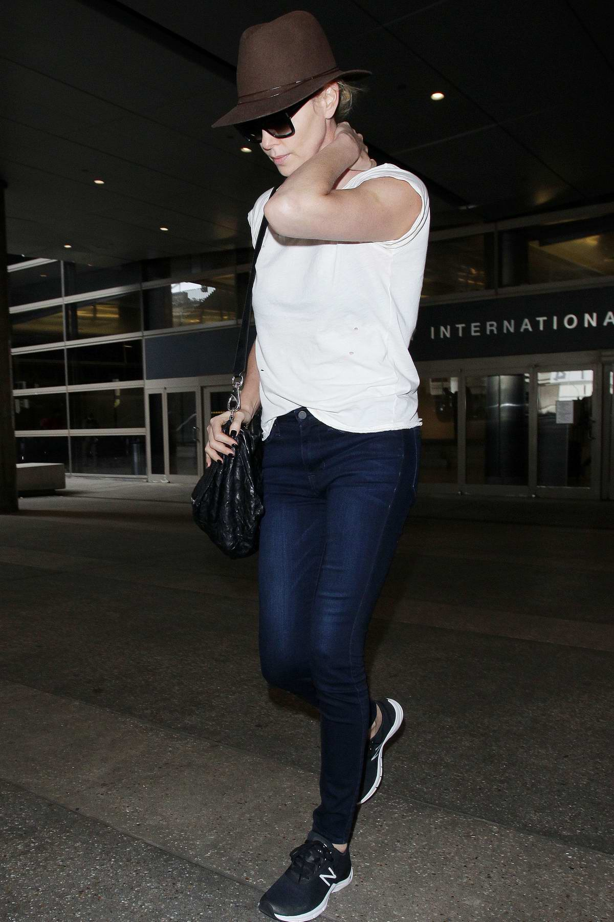 Charlize Theron keeps it casual in a white tee with blue jeans and a hat as she lands at LAX International Airport, Los Angeles