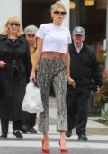 Charlotte McKinney looks chic in white crop top with patterned trousers and red high heels as she grabs some food to-go at La Scala in Los Angeles