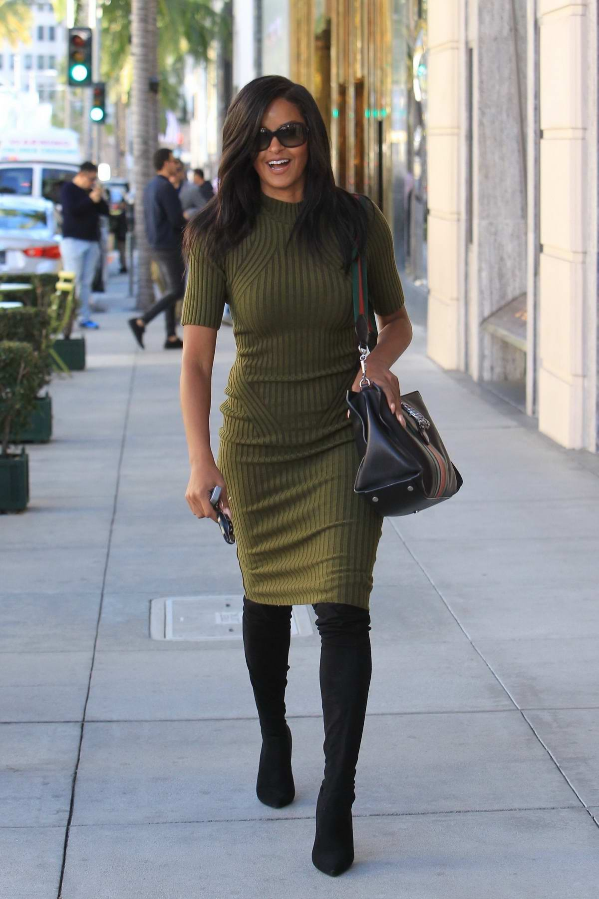Claudia Jordan wears an olive green dress with black thigh high boots while shopping in Beverly Hills, Los Angeles