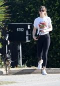 Dakota Johnson picks up some coffee while walking her dog before she hops on to Chris Martin's golf cart in Malibu, Los Angeles