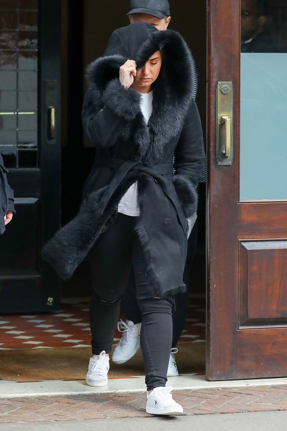 Demi Lovato wears a black fur lined coat as she leaves her hotel in New York City