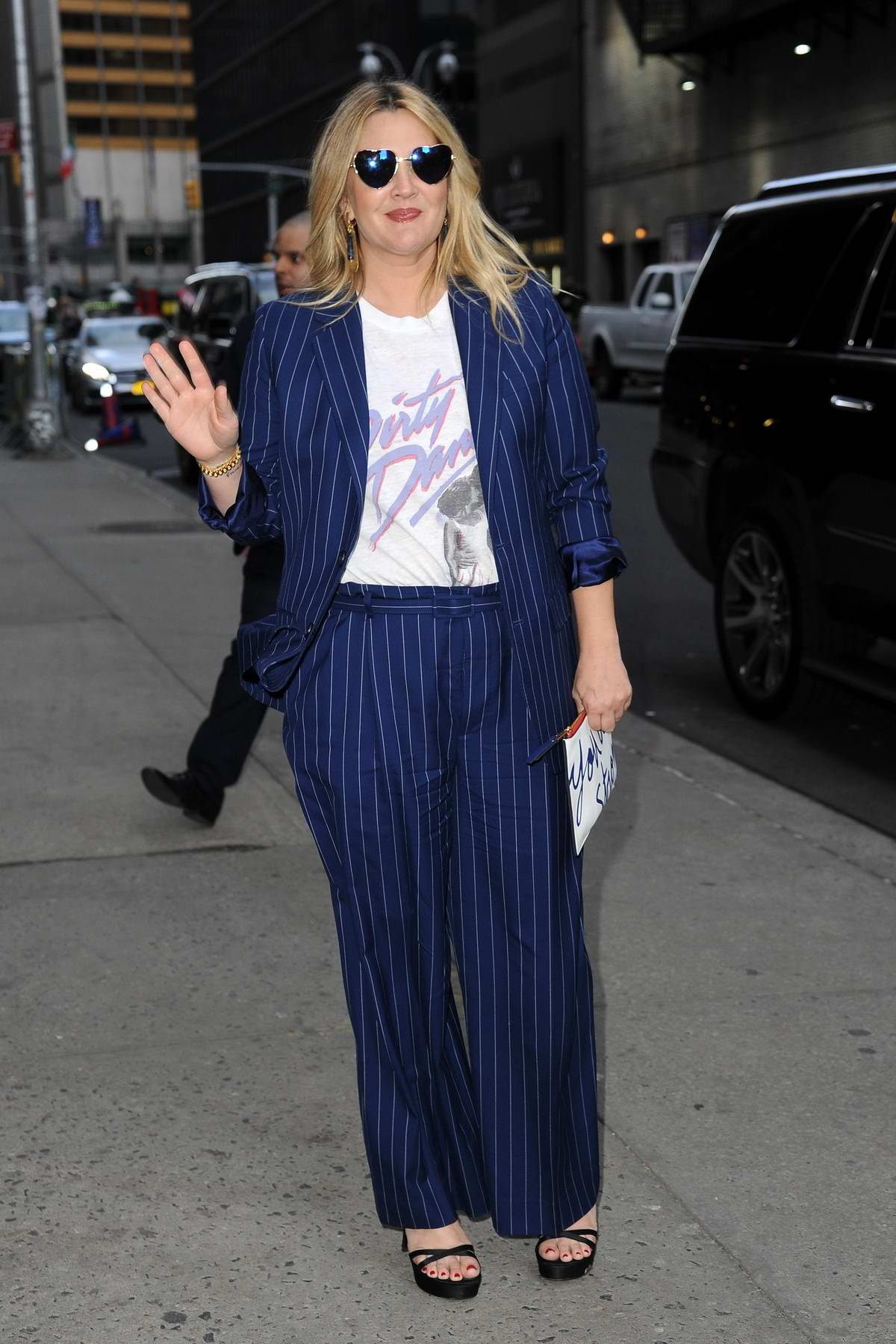 Drew Barrymore wears a pinstripe pantsuit with heart shaped glasses as she arrives at 'The Late Show with Stephen Colbert' in New York City