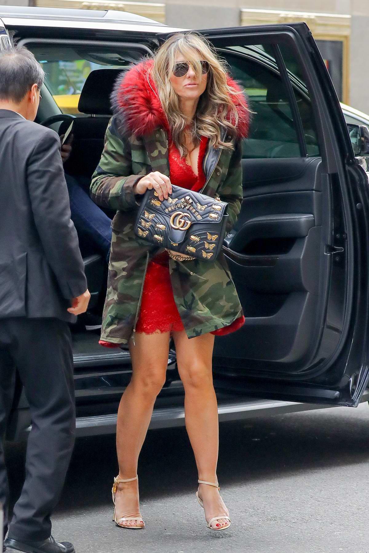 Elizabeth Hurley steps out in a short red dress with fur trimmed camo jacket in New York City