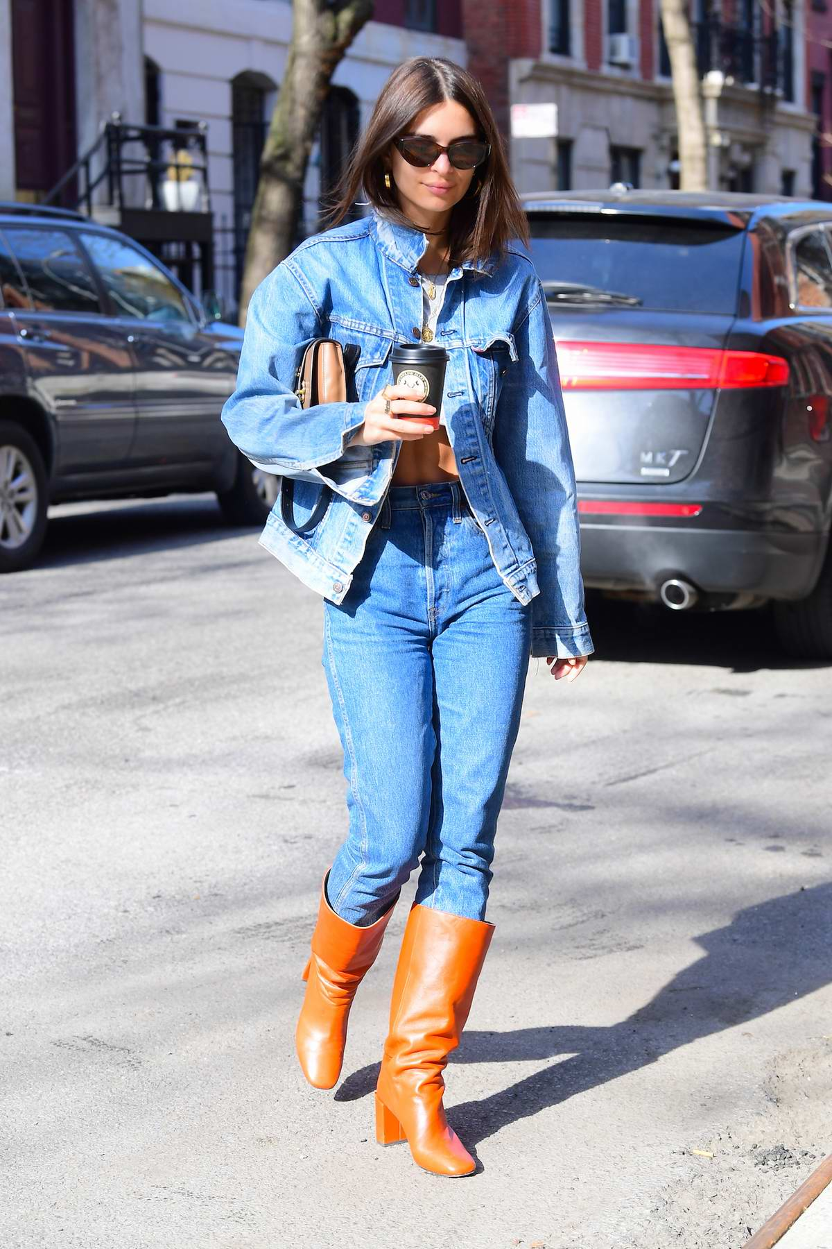 Emily Ratajkowski rocks an all denim look with knee high leather boots during a coffee run with her husband Sebastian Bear-McClard in New York City