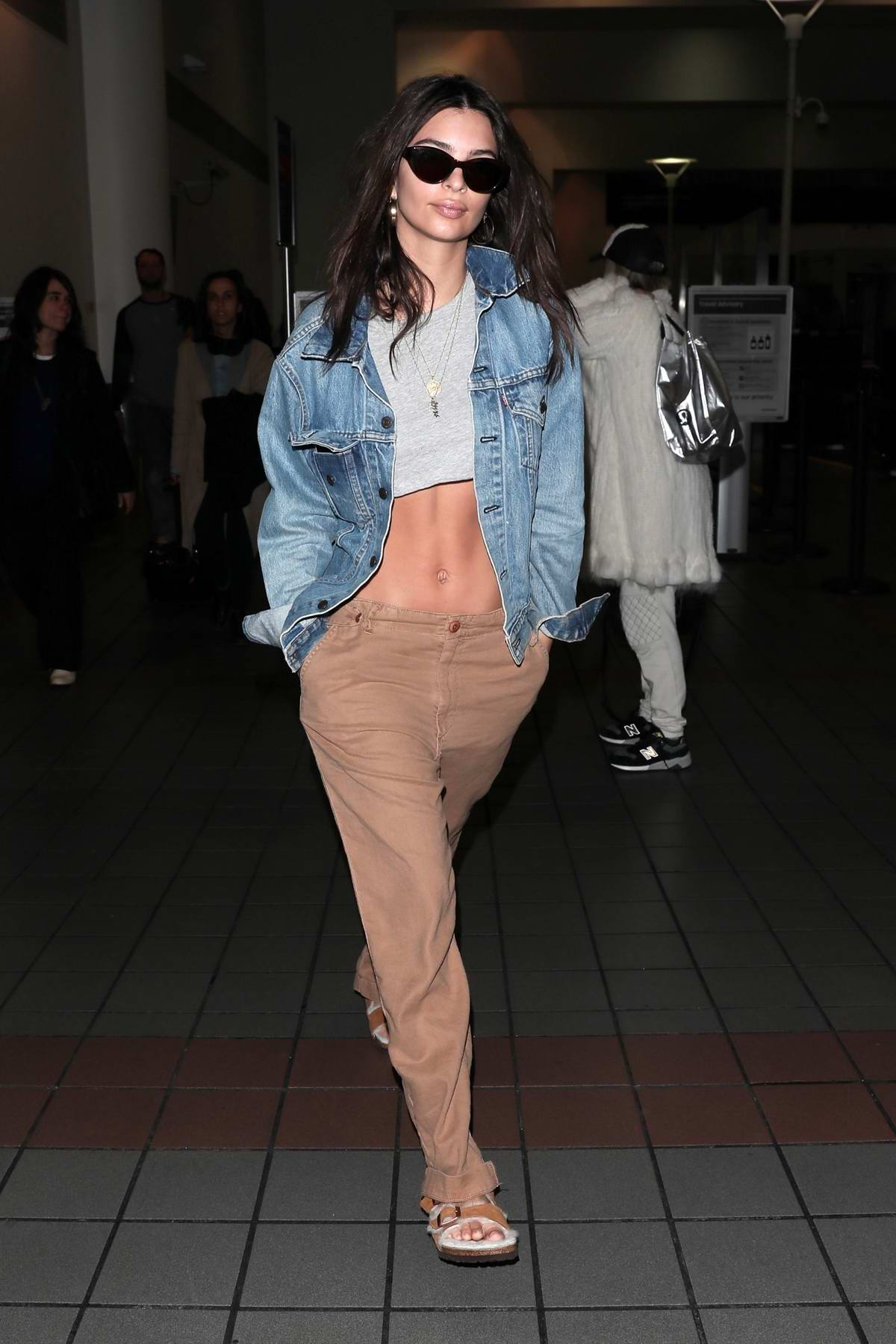 Emily Ratajkowski shows off her toned abs in a grey crop top with a denim jacket as she touch down at LAX airport, Los Angeles