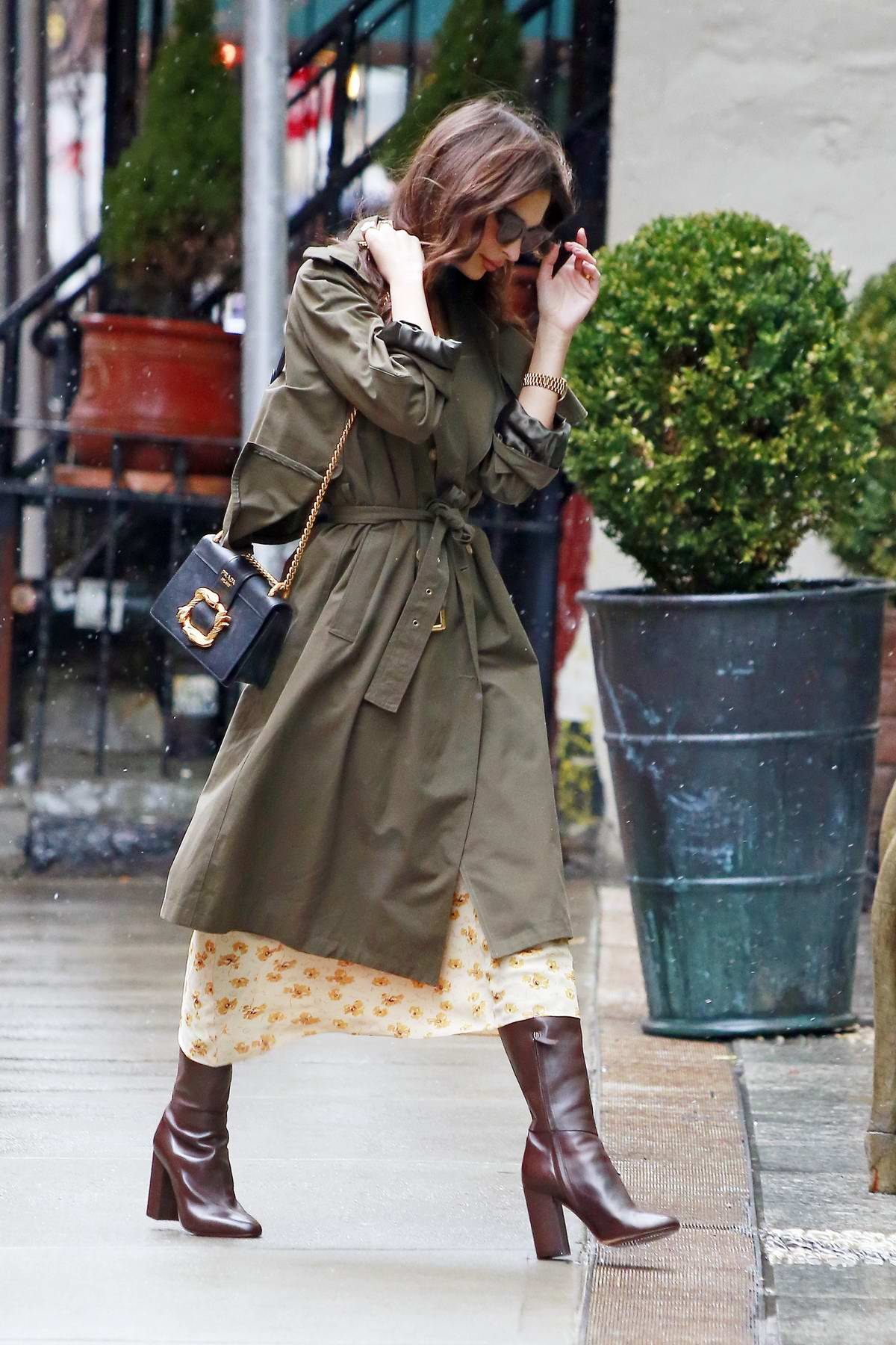 Emily Ratajkowski steps out in rain wearing a green trench coat in New York City