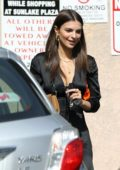 Emily Ratajkowski wears a black silk dress with orange boots while she visits a marijuana clinic in Los Angeles