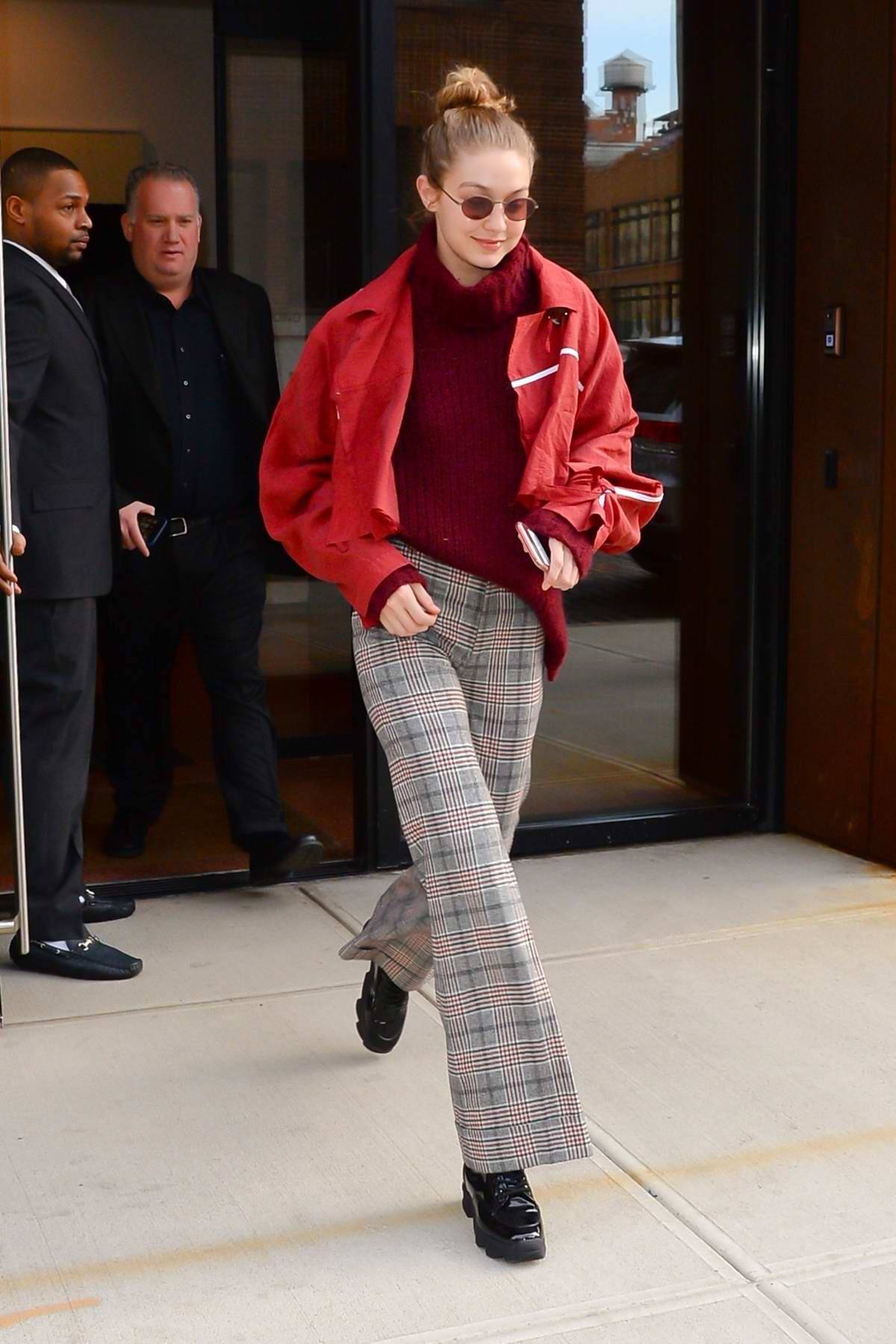 Gigi Hadid rocks a pair of checkered trousers teamed with red cropped jacket leaving her apartment in New York City