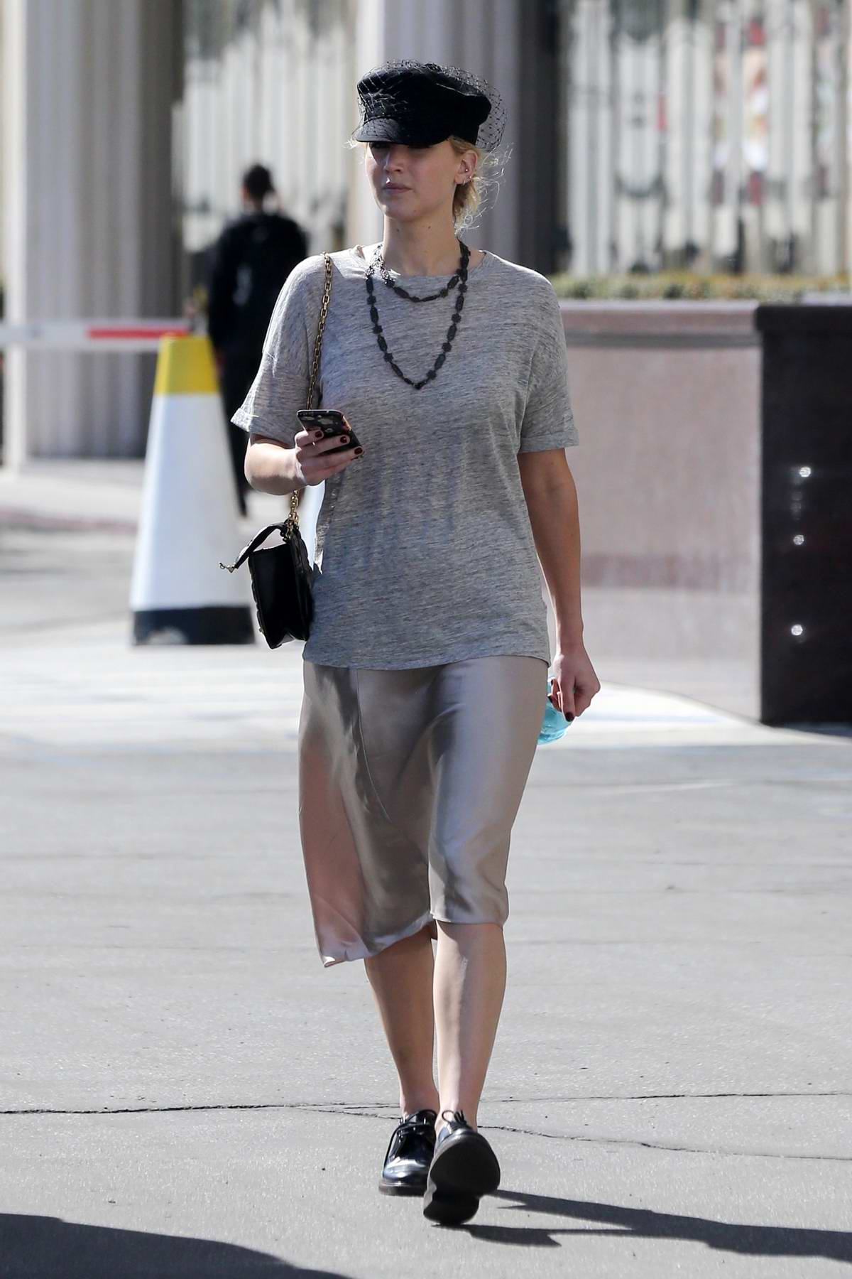 Jennifer Lawrence spotted in a grey top and satin skirt and black hat while out for a meeting in Westwood, California