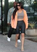 Kim Kardashian wears an orange jacket over a cropped vest top with leather biker shorts as she and Kanye West stops by a studio in Calabasas, California