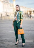 Olivia Culpo wearing Ronald van der Kemp pants and jacket, Valextra bag, Nina Ricci shoes during Paris Fashion Week, France