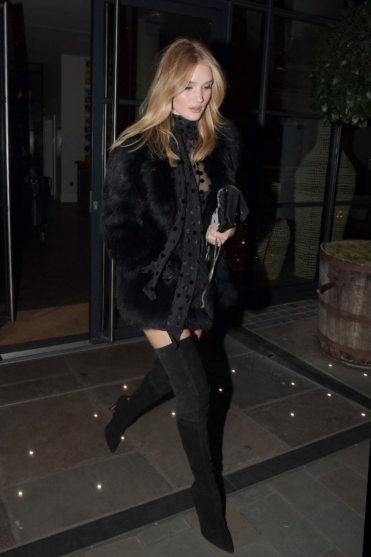 Rosie Huntington-Whiteley wearing a black fur coat with black thigh high boots while out to dinner with friends at Loulou's in London
