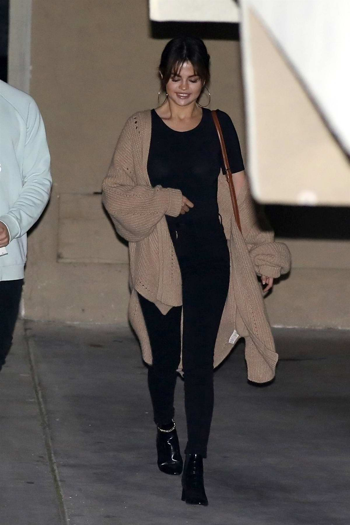 Selena Gomez spotted in a brown knit cardigan over a black top and jeans as she leaves church service in Los Angeles