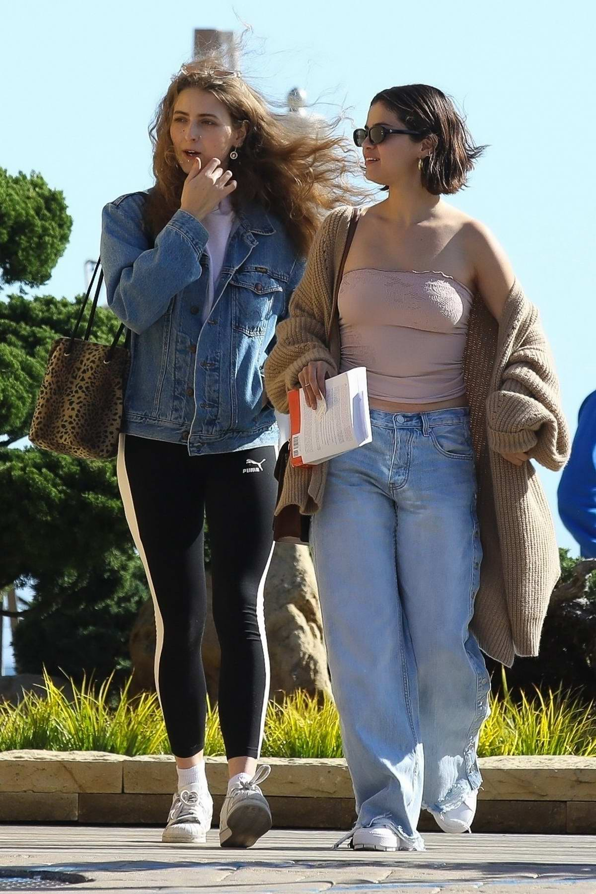 Selena Gomez steps out in a brown knit cardigan over a pink tube top and flared jeans as she grabs lunch with a friend at Nobu in Malibu, California