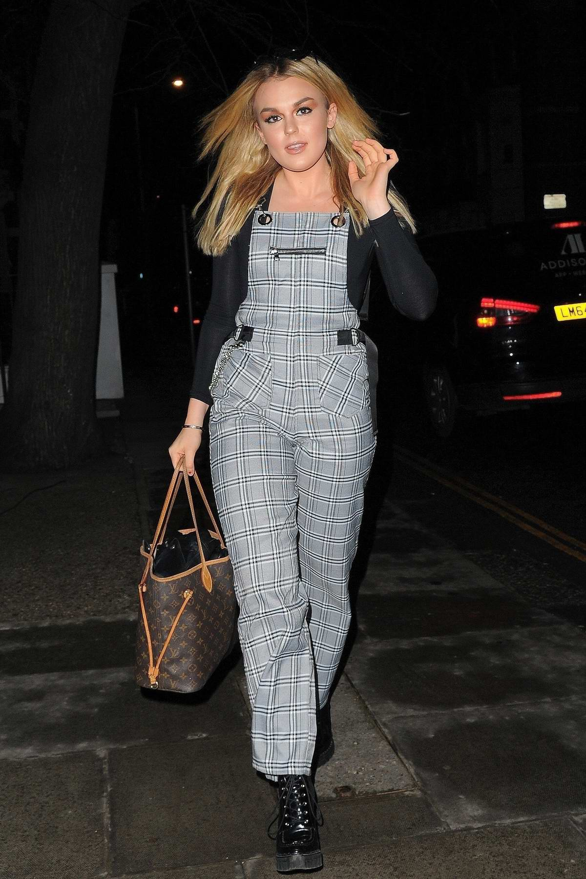 Tallia Storm wears a plaid dungarees over black top while attending the 'Feel Unique International Woman's Day Live Web Talk' in Islington, London