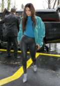 Kim Kardashian wears a teal jacket with 2XU black leggings while heading to a children's store with her friends in Los Angeles