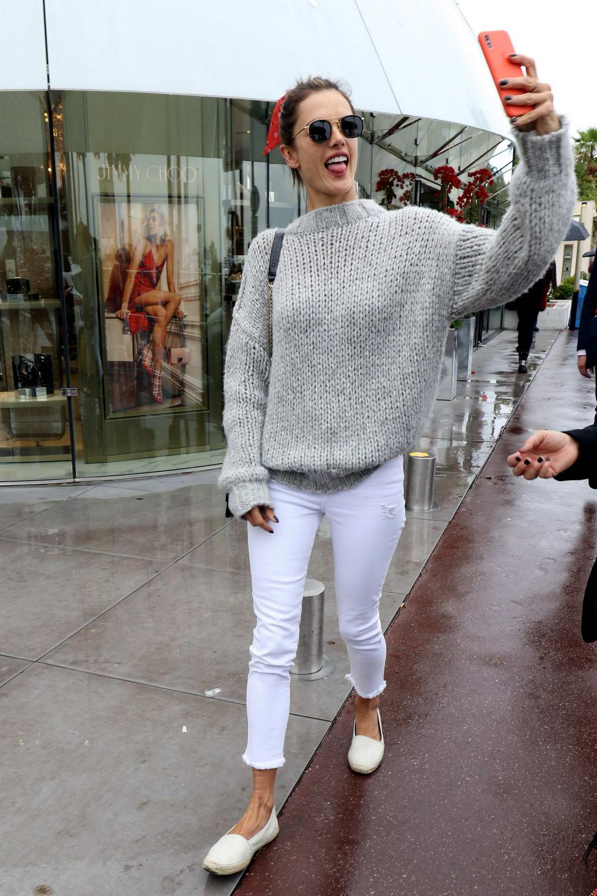 Alessandra Ambrosio steps out in a grey knitted sweater and white jeans while having fun with her phone in Cannes, France