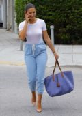 Tao Wickrath wears white top and blue Capri pants as she heads out of a restaurant in Miami, Florida