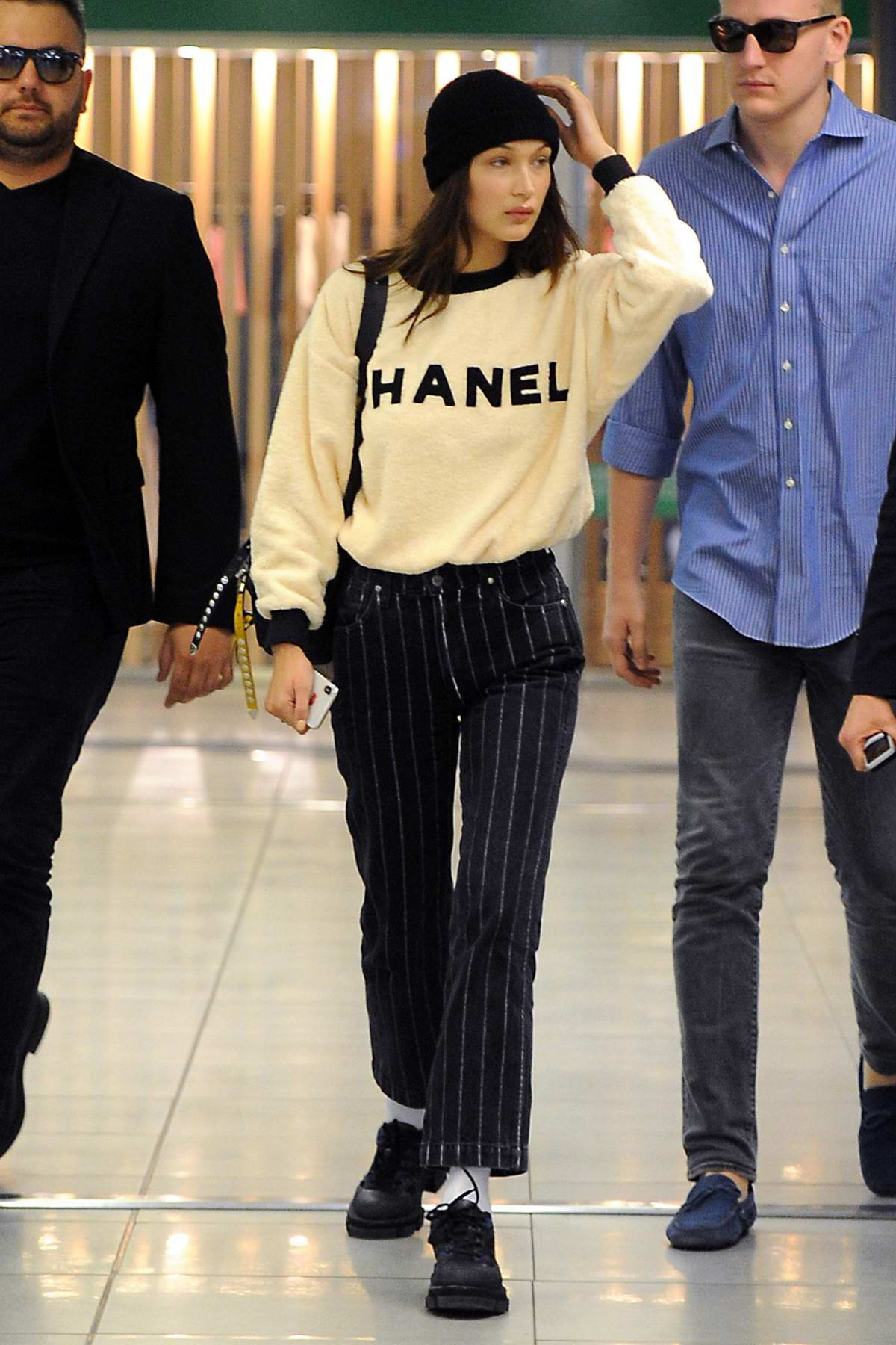 Bella Hadid rocks a Chanel sweatshirt and black striped pants as she arrives at the airport to catch a flight out of Milan, Italy