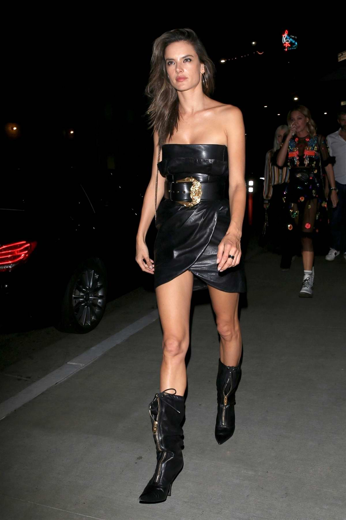 Alessandra Ambrosio wears black leather dress with matching leather boots as she leaves TAO restaurant after a night out with her friends in Hollywood, Los Angeles
