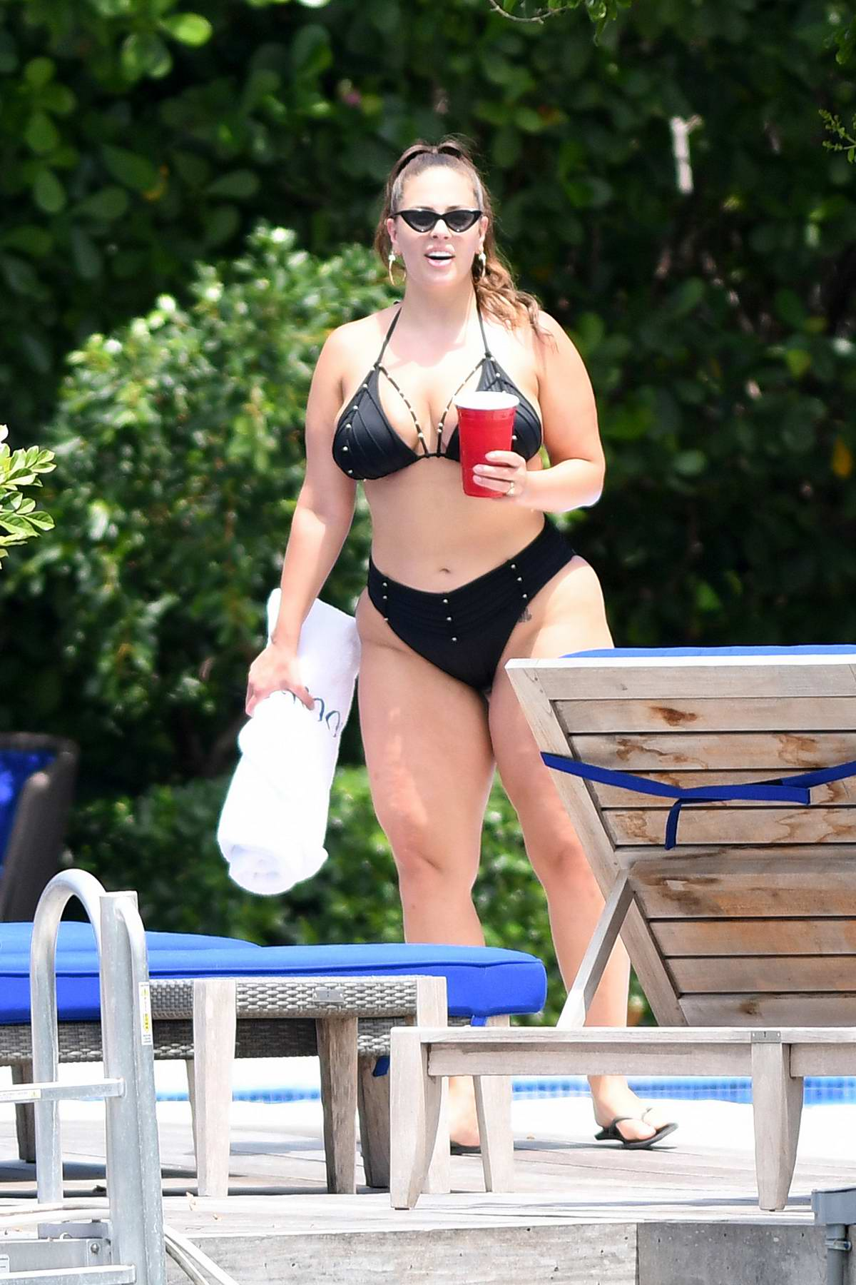 Ashley Graham in a black bikini enjoys a pool day with her friends in Miami, Florida