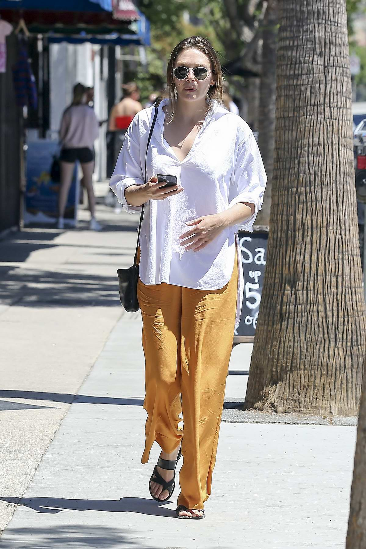 Elizabeth Olsen sports a comfy casual look in a white shirt and orange pants while out shopping in Los Angeles