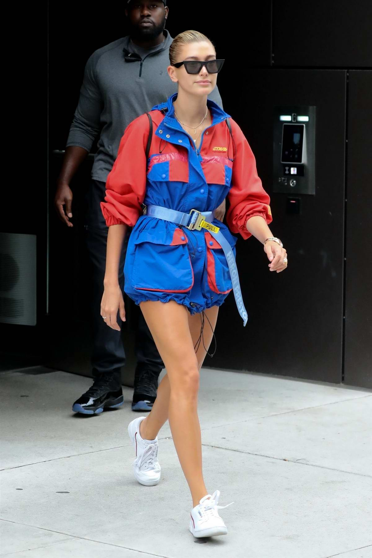Hailey Baldwin looks trendy in a red and blue Heron Preston jacket in Brooklyn, New York City