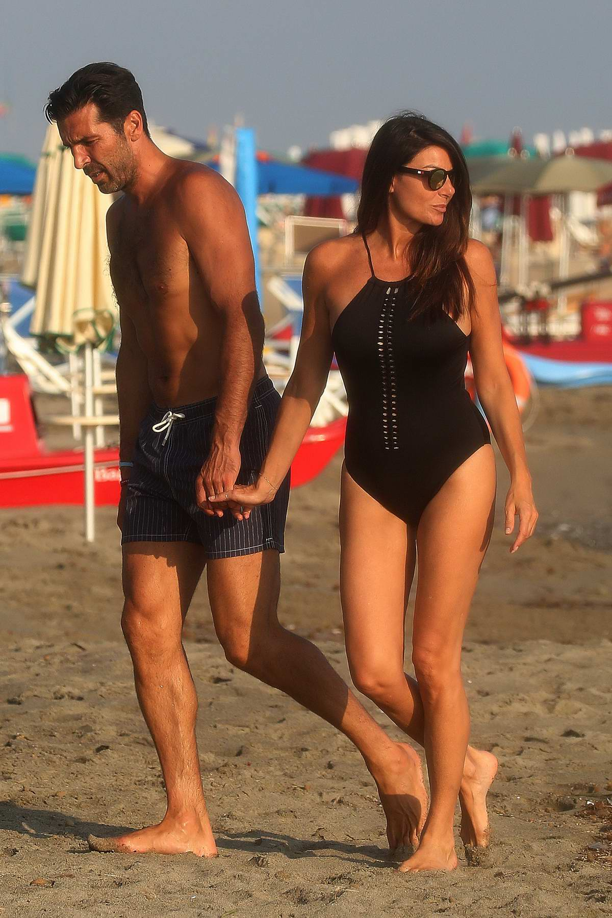 Ilaria D'Amico wears a black swimsuit while enjoying a romantic stroll on the beach with Gianluigi Buffon in Marina di Massa, Italy