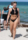Iskra Lawrence wears a black bikini while on the beach during Swim Week in Miami Beach, Florida