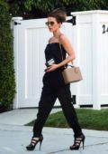 Kate Beckinsale gets ready on the go while walking to her car in an all black ensemble in Los Angeles
