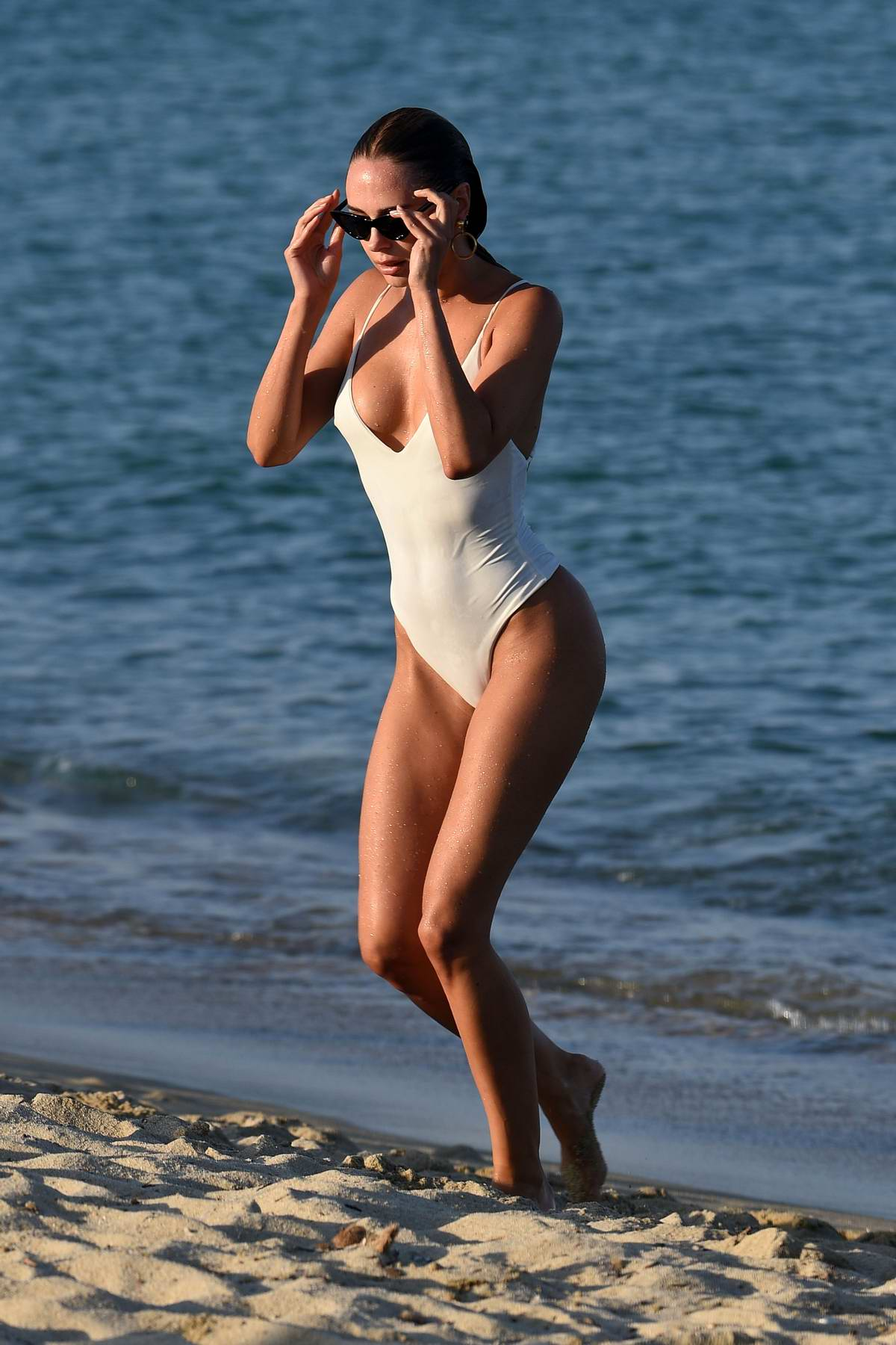 Kimberley Garner wears a white swimsuit as she hits the beach in Saint Tropez, France