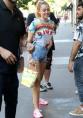 Miley Cyrus is all smiles while out wearing a Dior t-shirt, denim shorts and pink sneakers in New York City