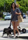 Nina Dobrev shows off her summer style in striped tee and denim shorts as she walked her dogs in Los Angeles