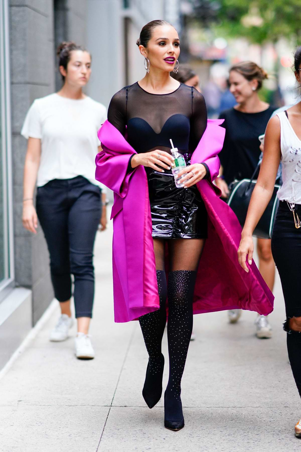 Olivia Culpo looks stunning in a sheer black outfit under a fuschia jacket in New York City
