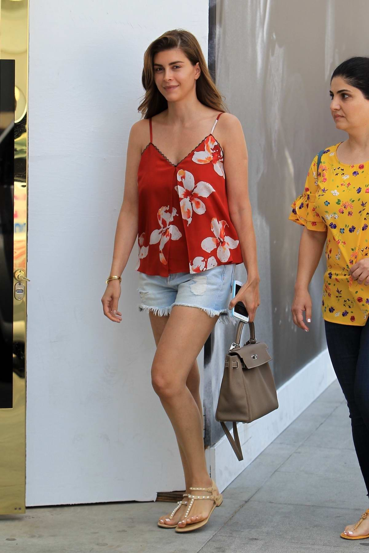 Shiva Safai seen wearing a red floral top with denim shorts while out in Beverly Hills, Los Angeles