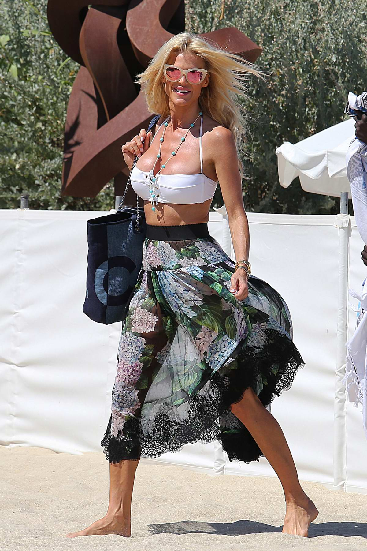 Victoria Silvstedt wears a white bikini top and floral skirt as she arrives at Club 55 in Saint Tropez, France