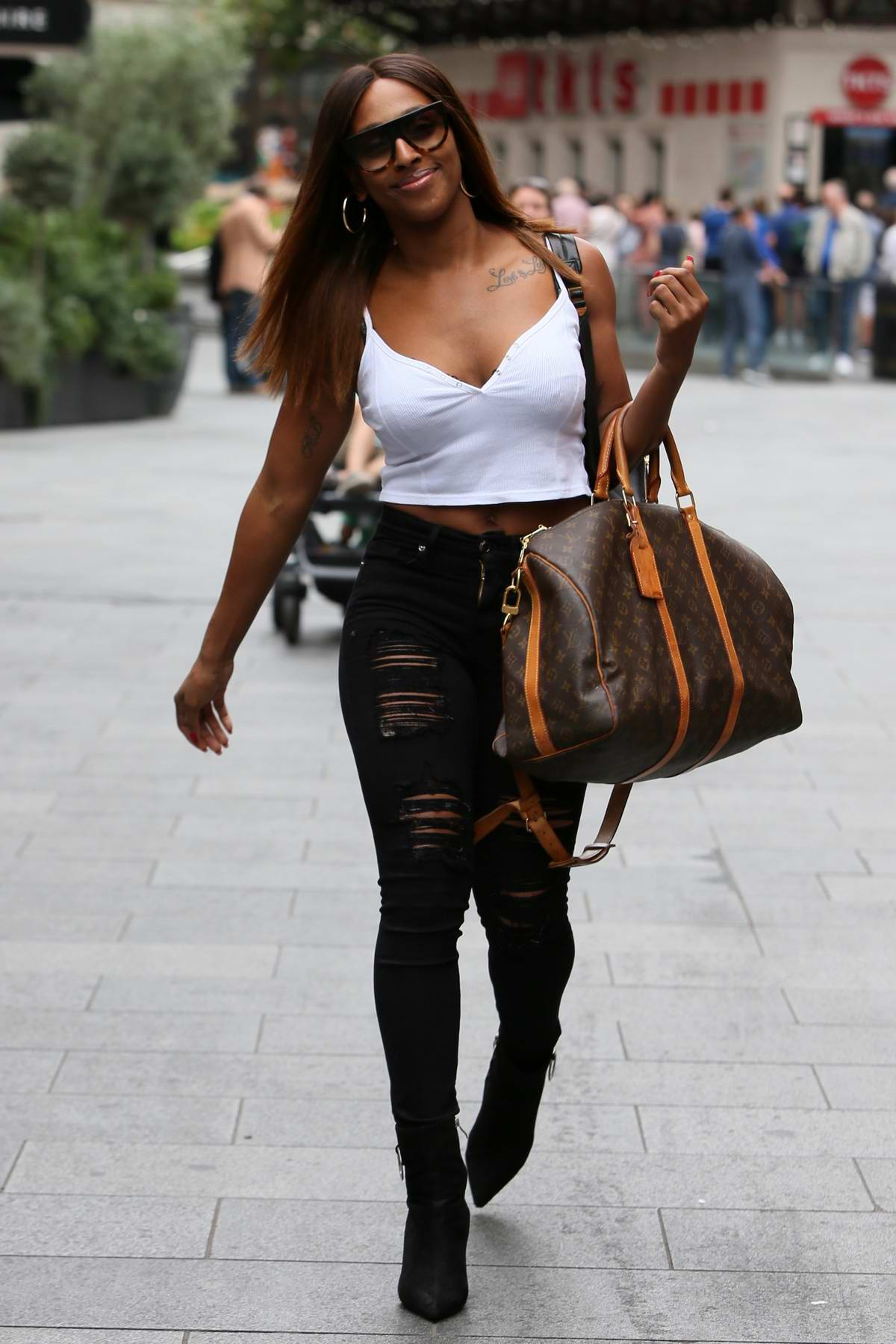 Alexandra Burke seen wearing a white top and black skinny jeans as she leaves Global Studios in London, UK