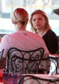 Chloe Grace Moretz grabs lunch with a friend on a terrace by the sea in Venice, Italy