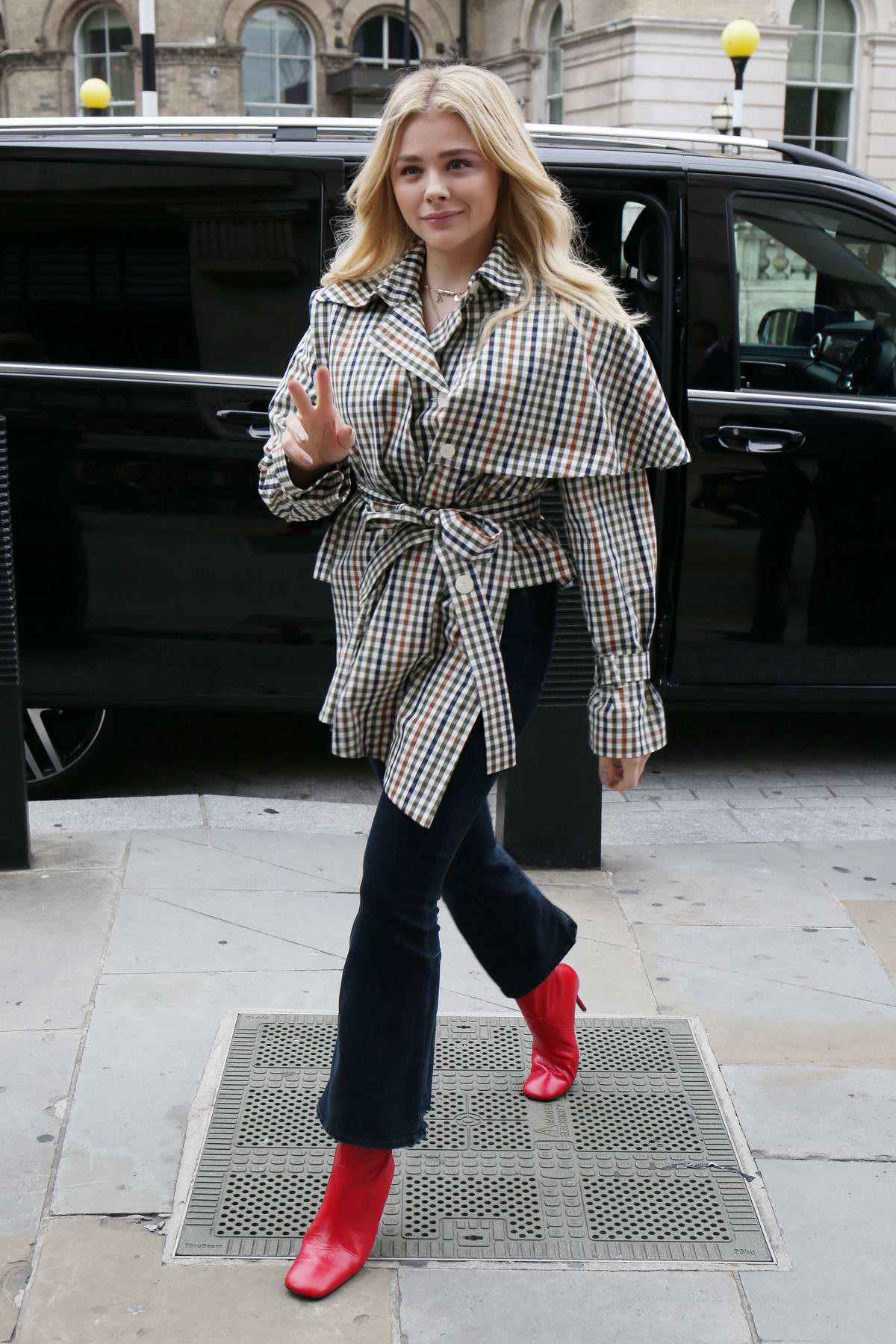 Chloe Grace Moretz steps out wearing a plaid coat and jeans with bright red boots in London, UK