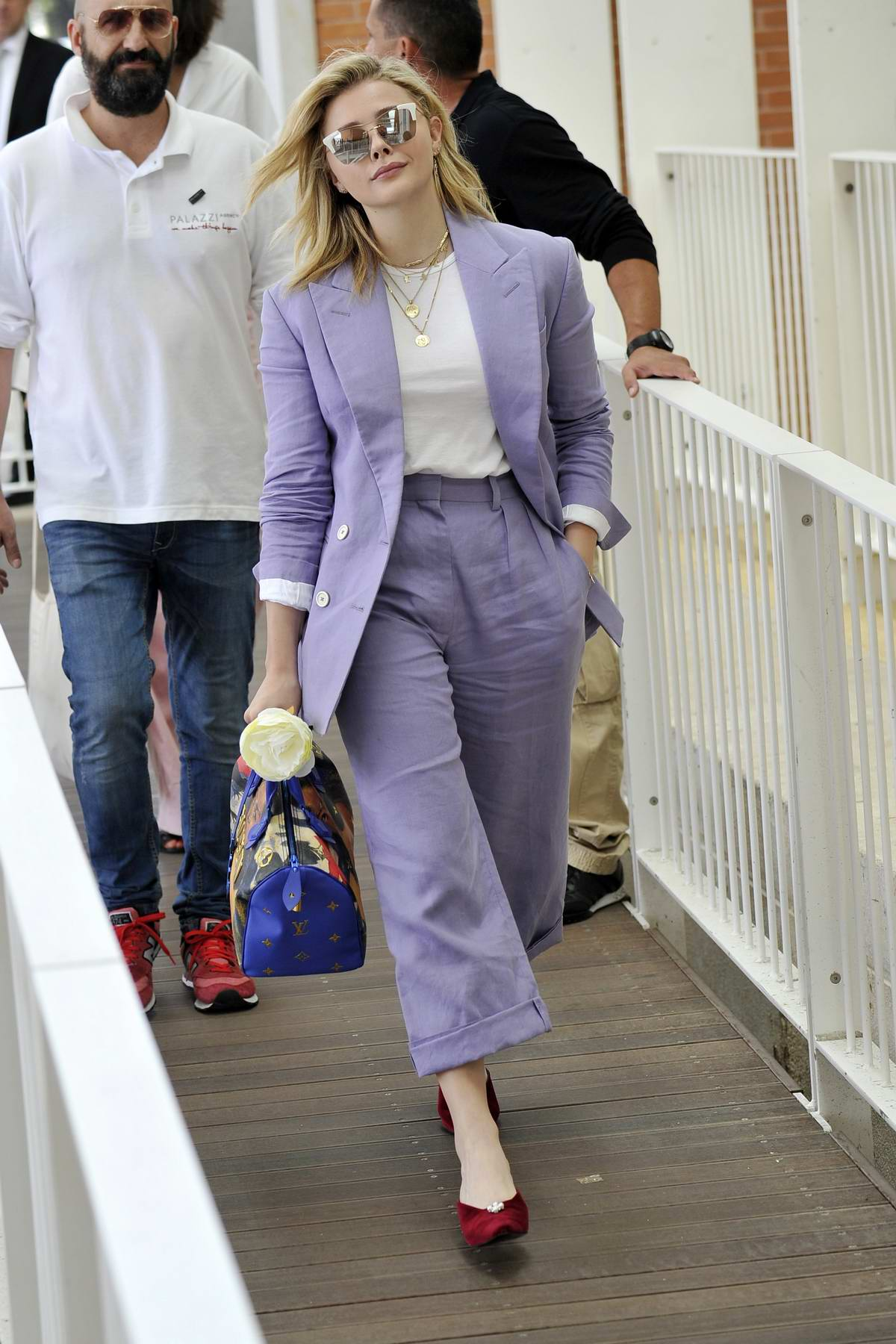 Chloe Grace Moretz wears a purple pantsuit while out during 75th Venice Film Festival in Venice, Italy