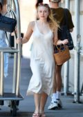 Dakota Fanning spotted in a white dress while pulling a luggage cart with her mother in New York City