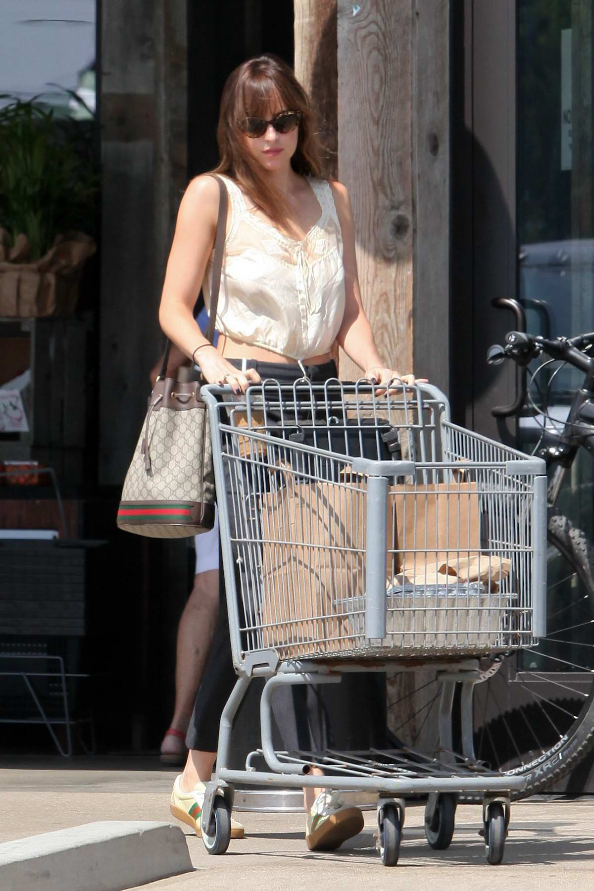 Dakota Johnson enjoys an iced coffee while pushing a shopping cart at Vintage Grocers in Malibu, California