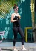 Dakota Johnson seen wearing a black tank top and leggings while picking up an iced coffee in Los Angeles