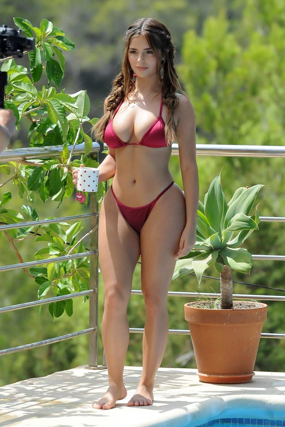 Demi Rose Mawby wears a red bikini during a photoshoot by the pool in Ibiza, Spain