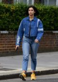 Dua Lipa rocks double denim with a pair of bright yellow sneakers while heading out in her new sports car in London, UK