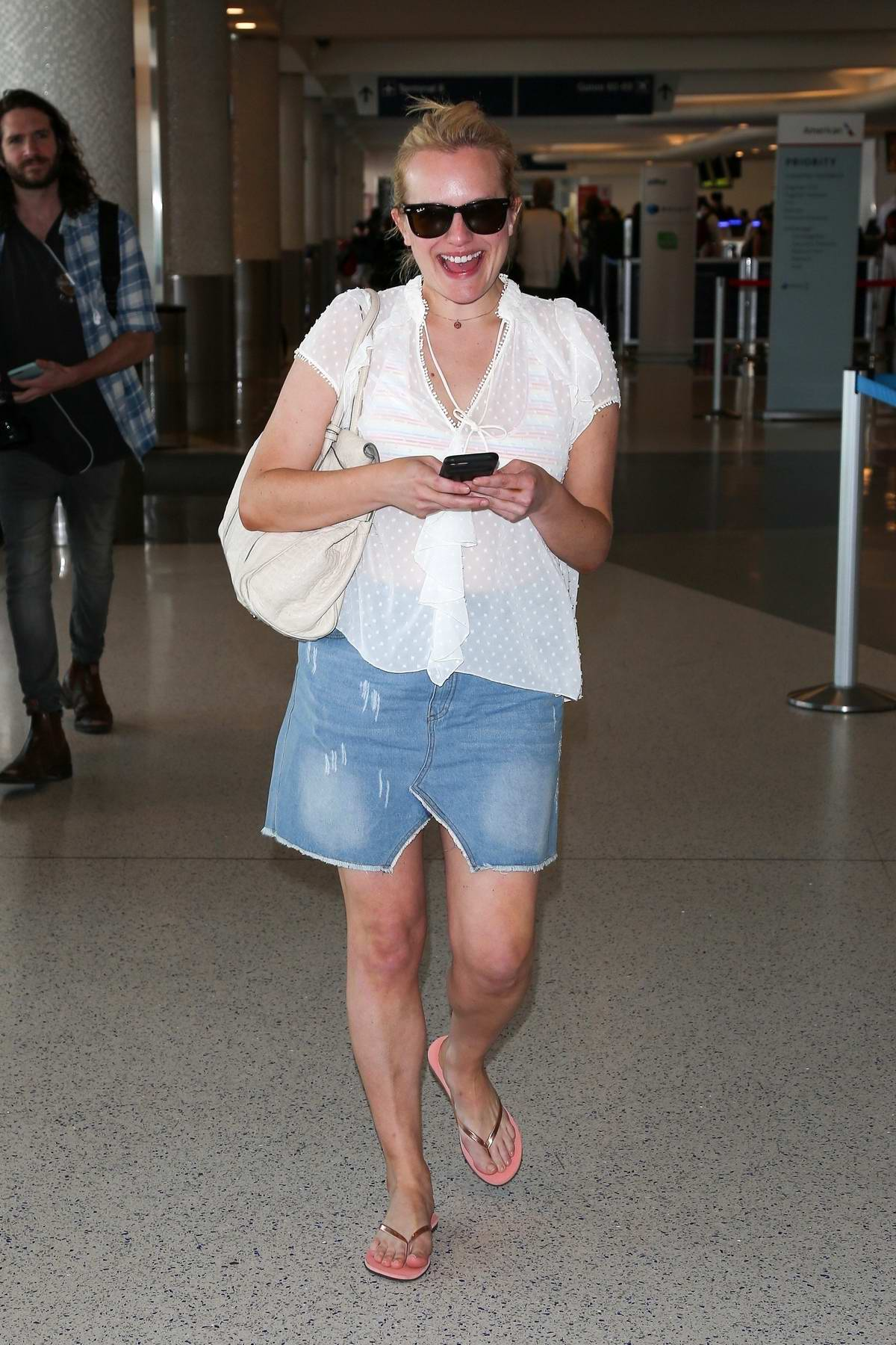 Elisabeth Moss is all smiles as she touches down at LAX airport in Los Angeles