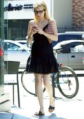 Emma Roberts looks cute in a little black dress as she grabs an iced coffee in Brentwood, Los Angeles