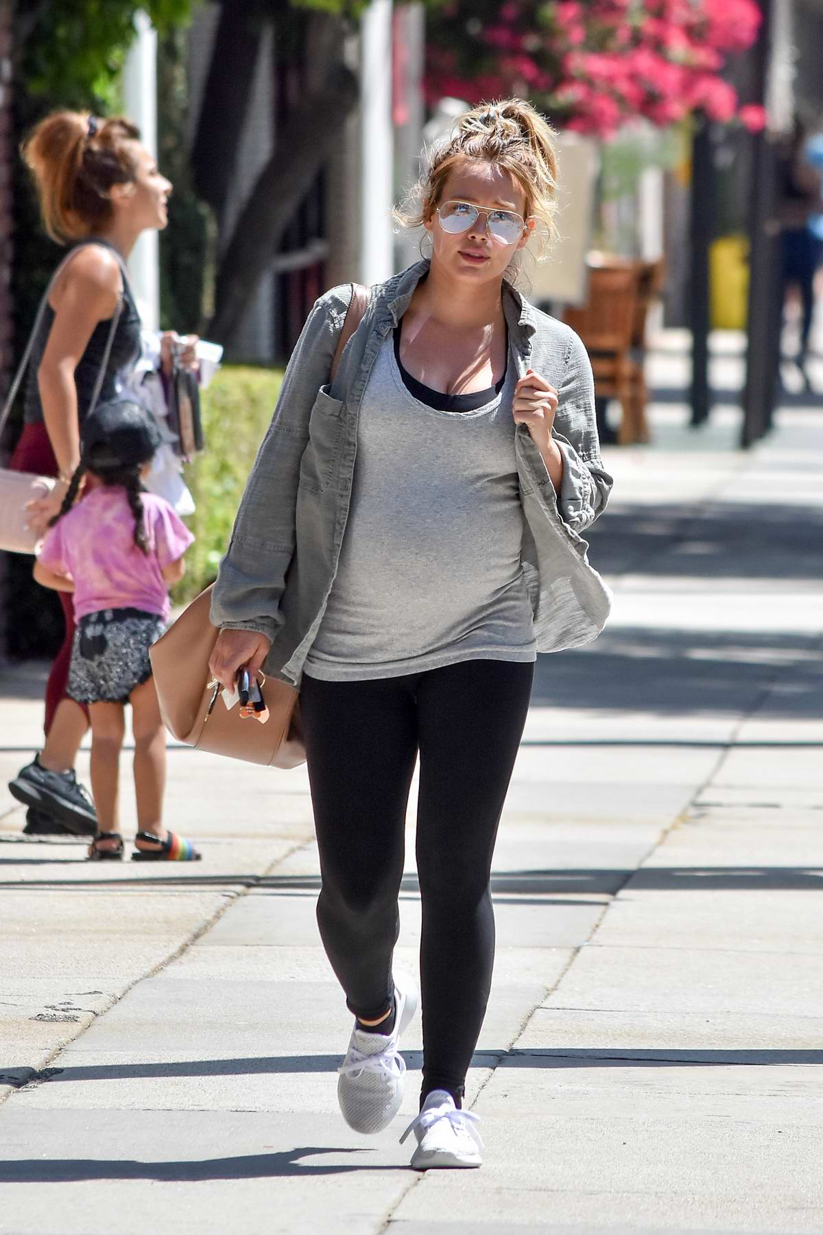 Hilary Duff rocks denim jacket over a grey tank top with black leggings as she leaves the gym in Los Angeles